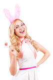 My favorite color is pink!. Beautiful young blond hair woman with rabbit ears holding lollipop and smiling while standing isolated on white background royalty free stock image