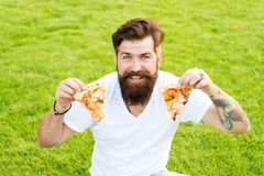 My favorite pizza. summer picnic on green grass. pizza weekend. fast food. bearded man hipster eat pizza. happy man. My favorite pizza. summer picnic on green royalty free stock photography