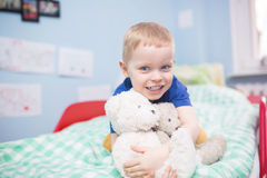 My favorite toys. A photo of small boy sitting on the bed and hugging teddy bears Royalty Free Stock Photo