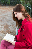 My favourite book. Redhead reading her favourite book , romance novel in the city park, while siting on a bench Stock Photos