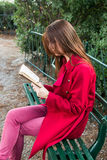 My favourite book. Redhead reading her favourite book , romance novel in the city park, while siting on a bench Stock Images