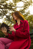 My favourite book. Redhead reading her favourite book , romance novel in the city park, while siting on a bench Royalty Free Stock Photo