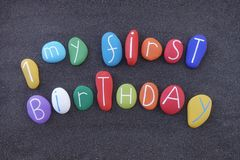 My first birthday celebrated with a composition of colored stones over black volcanic sand stock photography