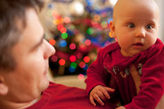 My first christmas #1. Baby in a red babywear with his father. Christmas lights in the background Stock Images
