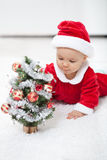 My first christmas. Baby girl in santa outfit with small decorated tree Stock Photography