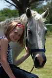 My first pony. A white caucasian girl child bonding with her white pony Royalty Free Stock Photography