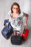 Is my flight canceled?. A picture of a young woman waiting with many pieces of luggage at the airport royalty free stock photography