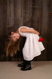 My flower. A young girl bent over holding a red rose royalty free stock photos