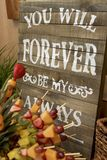 My Forever Always. Rustic wooden anniversary sign with white, stenciled words reading You will forever be my always.  Spears of fresh fruit slices in the Royalty Free Stock Image