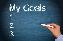 My goals list. My Goals concept with a checklist on a blue chalkboard with a female hand holding a chalk - business, planning, vision or management concept stock photography