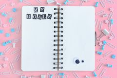 My Goals. A sprinkler with white pages. The stationery is in disarray. Staples, paper clips and asterisks are randomly. Scattered on a pink background. Bright stock photography