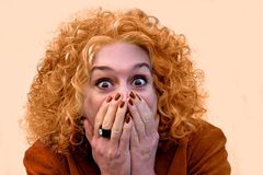 My god, I am orange. Shocked and frightened woman after looking in the mirror. Her hair has turned orange after dyeing royalty free stock photography