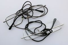My grandfather`s old glasses are on a white table. Simple steel frame of plastic glasses and neck straps stock image