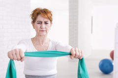 My health is worth this effort. Mature woman exercising with tape in light interior Stock Image