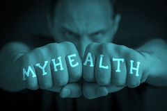 MY HEALTH written on an angry man's fists. MY HEALTH written on the fingers of an angry man's fists. Turquoise colored. Message concept image Royalty Free Stock Photos