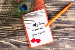 My heart is ever at your service. Text in notebook with peacock feather , pen and heart shape on wood royalty free stock photo