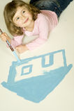 My home. Little girl painting blue house stock photo