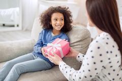 Loving mother giving her daughter a gift. For my honey. Pretty alert curly-haired girl sitting on the sofa and smiling and her mother giving her a gift Stock Photography