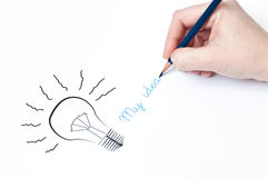 My idea. Woman's hand is drawing a light bulb. Idea concept Royalty Free Stock Photography