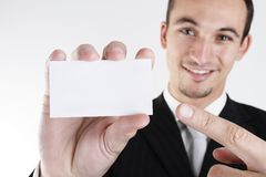 My info is on the card. A young business man pointing with his finger to a blank card Royalty Free Stock Images