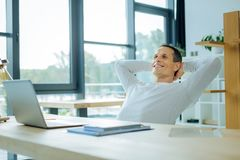 Delighted positive man relaxing at work Royalty Free Stock Photos