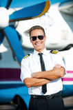 My job is my passion. Confident male pilot in uniform keeping arms crossed and smiling while standing in front of the airplane Royalty Free Stock Photo