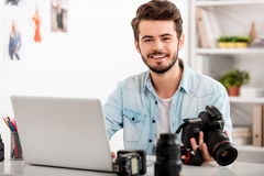 My job is my passion. Handsome young man holding camera and smiling while sitting at his working place Stock Photo