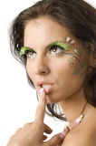 My lip. Cute and sensual brunette with a finger against the lip and green artificial eyelashes royalty free stock photography