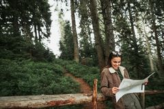 Beautiful young lady reading map while leaning against wooden fence stock photos