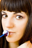 My lollipop. Extreme close-up of a young woman licking a lollipop. Portrait orientation royalty free stock photo