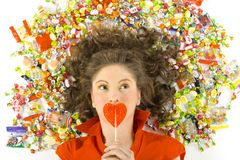 My lollypop. Young, beautiful woman lying on floor among candys with lollypop in hand. Thinking of something, front view. White background Royalty Free Stock Photo