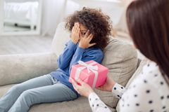 Loving mother holding a gift for her daughter. For my love. Nice joyful curly-haired girl sitting on the sofa and closing her face with her hands and her mother Royalty Free Stock Photos