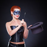 My Magical Hat. Beautiful redhead Female magician in dark Royalty Free Stock Photography