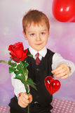 For my mom. Little boy giving red rose and heart for mom-focus on flower Royalty Free Stock Photography
