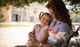 In my mom`s embrace is the most beautiful. Mother and daughter sitting in park on bench. Close up. copy space royalty free stock photo