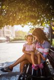 In my mom`s wings is beautiful. Mother and daughter sitting in park on bench. Close up. copy space royalty free stock images