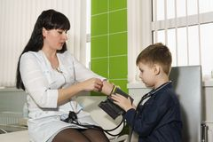 My moms a nurse teaches son to measure the pressure. Acquaintance with my mothers profession royalty free stock photography