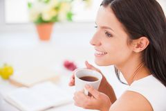 My morning coffee. Side view young smiling woman sitting in bed and holding a cup while covered with blanket Royalty Free Stock Image
