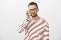 My mouth is fortress, count on me. Portrait of serious funny caucasian man in glasses, making gesture with hand, zipping. Lips, promising to keep secret Royalty Free Stock Photo