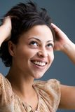 My new haircut. Smiling mulatto woman is touching her hair Royalty Free Stock Images