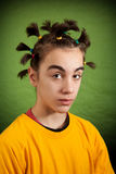 My new hairstyle. Young man proudly shows his new hairstyle.  on green background with a dark vignette Stock Photography