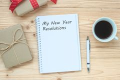My New Year Resolutions word with notebook, black coffee cup and pen on wooden table, Top view and copy space. New Start, Goals, S royalty free stock photography
