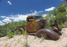 My next ride - Corroded Oldtimer grow into the Landscape. Rusted and corroded old car grown into the landscape near Bryce Canyon, Arizona, United States of stock images