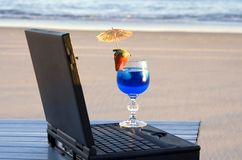 My office view. Laptop and cocktail next to the laptop, with the beach in the background royalty free stock image