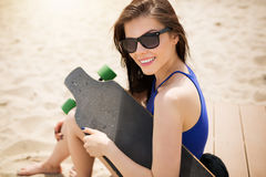 This is my passion. A photo of young, beautiful woman in sunglasses sitting on the beach and holding a longboard. She's smiling happily Royalty Free Stock Photos