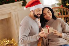 Happy woman cuddling husband giving her Christmas present Royalty Free Stock Images