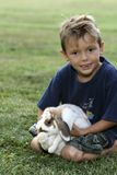 My pet. Little boy and pet rabbit on the grass Royalty Free Stock Image