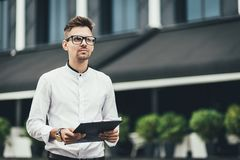 My plan must succeed. Business man in street holding document and thinking royalty free stock image