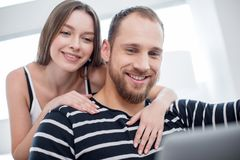 Inspired woman hugging her man. My precious. Beautiful happy long-haired young women hugging her boyfriend and smiling while he using a tablet Royalty Free Stock Photos