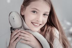 Inspired girl hugging her toy. My precious. Beautiful long-haired grey-eyed girl smiling and beaming with happiness while hugging her toy Royalty Free Stock Image